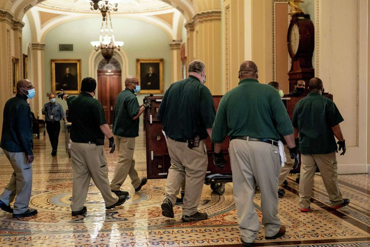 Capitol workers move furniture at the Capitol in Washington on Monday, Feb. 8, 2021, as the Capitol is prepared for the Senate impeachment trial of former President Donald Trump, scheduled to begin on Tuesday. (Erin Schaff/The New York Times)