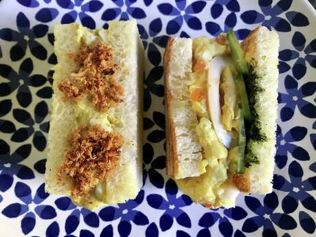 "Curried egg salad sando with fried apple and vegan ""floss,"" left; two-egg salad sando with cured egg, salmon roe, shiso pesto and cucumber, right"