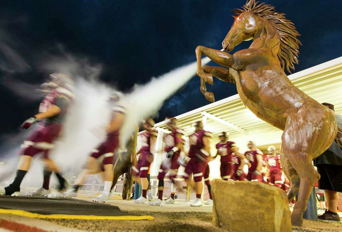 The Magnolia West football team takes the field before a District 20-5A high school footbal game against rivial Magnolia at Mustang Stadium Friday, Oct. 14, 2016, in Magnolia.