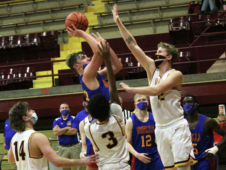Roxana's Gavin Huffman (middle) shoots over EA-WR's Andrew Oliger, with the Oilers' Ahmad Allen (3) and Spencer Slayden (14) watching the shot in the second half Saturday at Memorial Gym in Wood River. Photo: Greg Shashack / The Telegraph