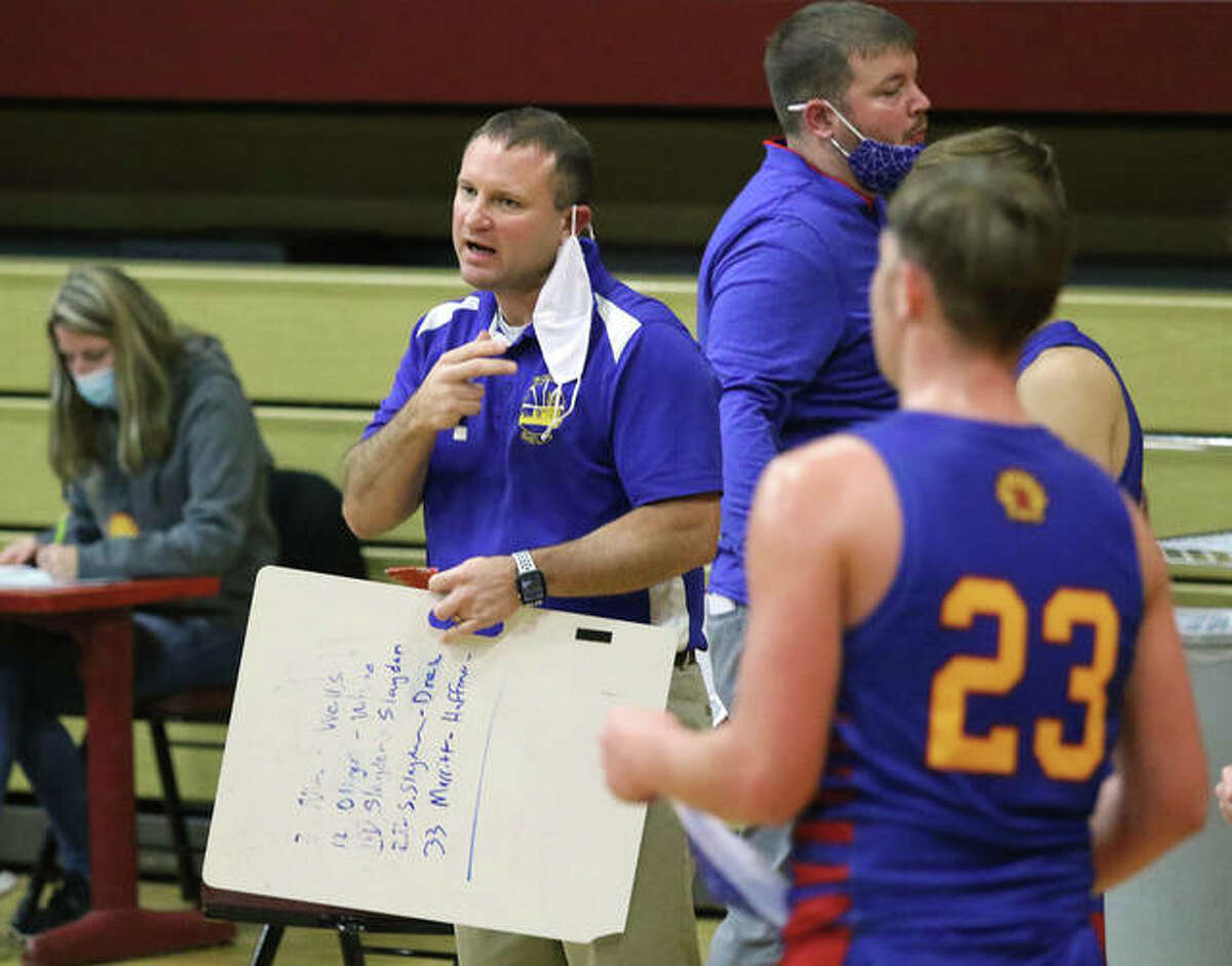 Roxana coach Mark Briggs talks with his team during a 'mask break' timeout that comes midway through each quarter in basketball games this season.