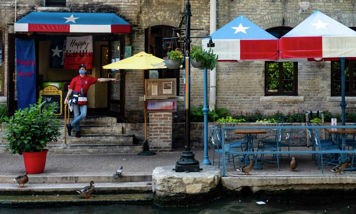 A server waits for customers at the Republic of Texas restaurant on the San Antonio River Walk in August.
