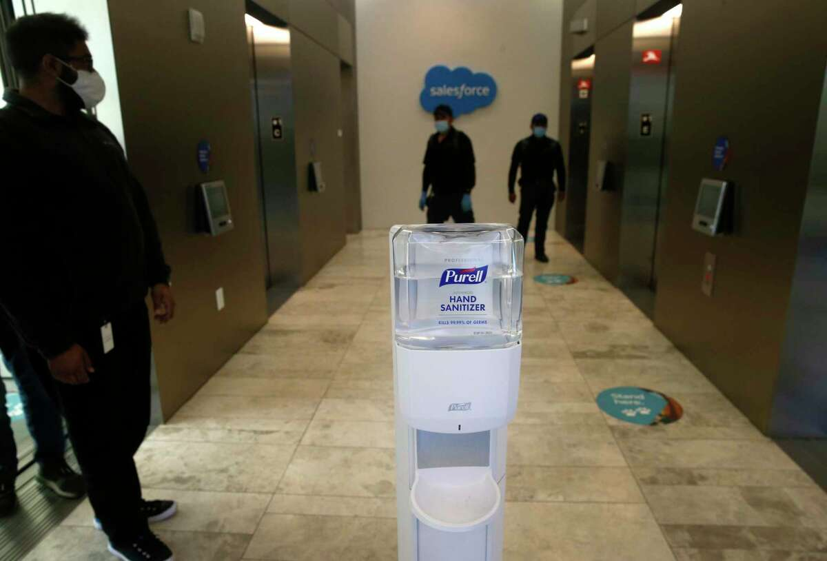 Maintenance workers emerge from elevators at the Salesforce East office tower in October 2020.