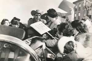 """Screaming autograph-seeking Gladwin teenagers mob the car carrying Cowboy Benny, Mrs. Clarey, right, and Miss Mullins, head down, as the driver tries to reach the officials' stand at the close of the parade. School children out of classes for the event carried signs reading, """"yup"""" and nope."""""""