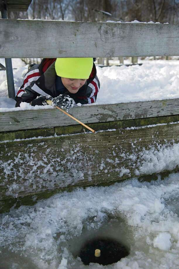 A young angler during a past Winter Free Fishing Weekend waits excitedly to see what will pop up from the icy water. Everyone can fish for free-- no license needed-- during the 2021 Free Fishing Weekend, Feb. 13 and 14. (Courtesy photo/David Kenyon/Michigan DNR) / 2012 State of Michigan