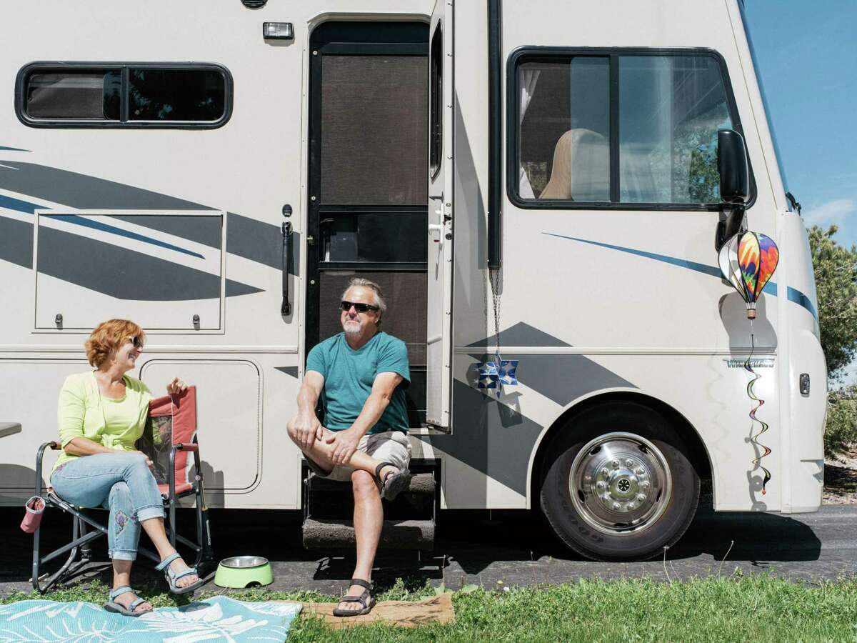 Tom and Mona Mesereau sit in the sun outside their Winnebago in Evergreen, Colo., on May 30, 2020. Recreational vehicles were gaining in popularity before the coronavirus pandemic, but now, with travel restrictions loosening, a surge of travelers is drawn to the relative solitude that RVs offer. Elizabeth Eddins, the executive director of Visit The Woodlands, said use of state parks and RV rentals were on the rise in Texas. She also said driving visitors come for weddings, reunions or other events hosted at hotels in the community.