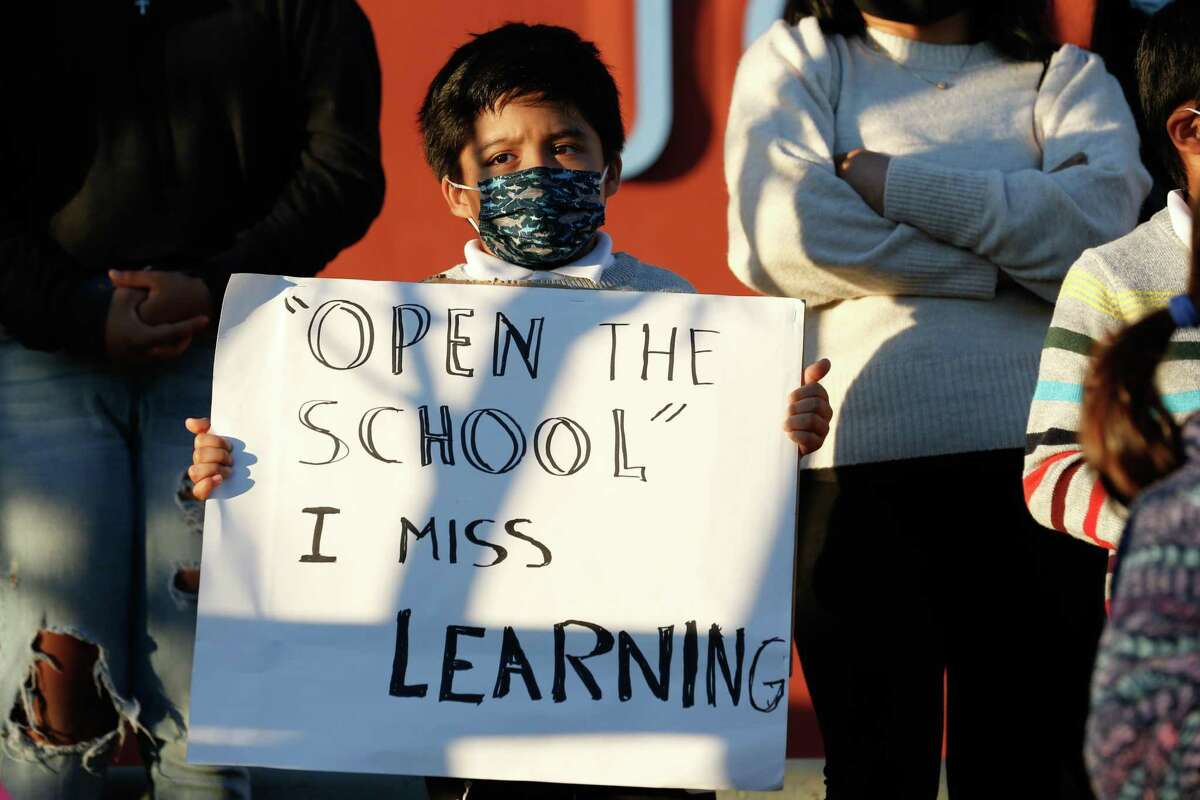 Brian Martinez, 7, holds a sign as families and city officials including Mayor London Breed, attend a press conference with the organization Decreasing the Distance to support the reopening of San Francisco's public schools on Thursday, February 4, 2021.