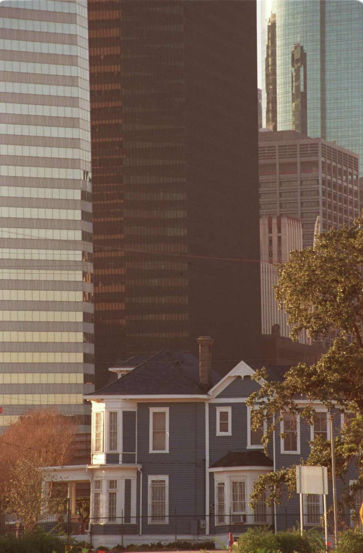 Downtown buildings loom over the Cohn House at its previous location at 1711 Rusk in 2001.