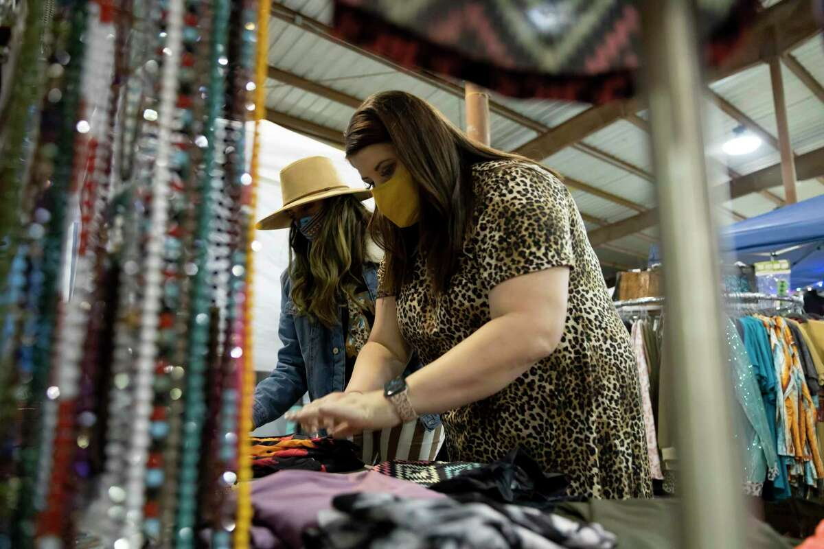Alanna Puckitt, right and Blaze Rucker, left arrange items from their shop, Rustic Cactus Boutique, during the Humble Rodeo at the Humble Civic Center & Arena Complex, Saturday, Feb. 6, 2021, in Humble. Rustic Cactus Boutique is based and Hempstead and was the first year they've attended the event.