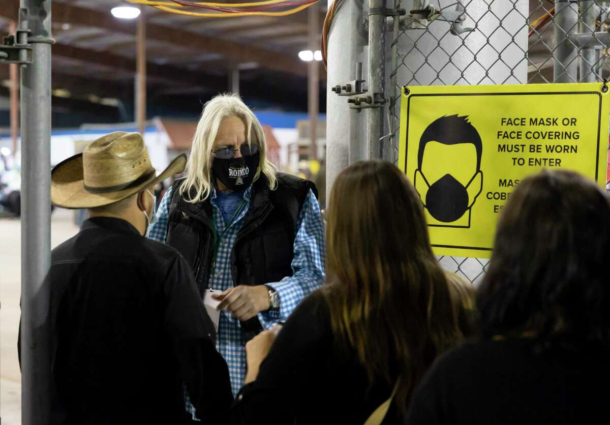 Dorsey Woods, center, checks people in during the Humble Rodeo at the Humble Civic Center & Arena Complex, Saturday, Feb. 6, 2021, in Humble. Face masks and social distancing were encouraged during the event to prevent the spread of the COVID-19 virus.