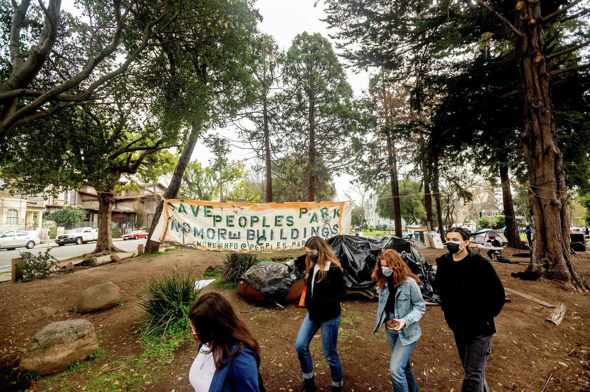 Students walk past a banner at People's Park. They are protesting plans to use site for student housing.
