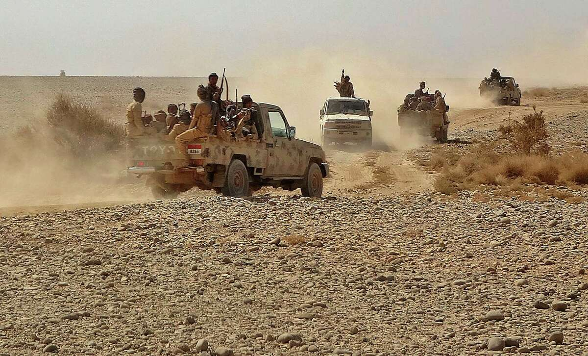 Fighters ride in pickup trucks as forces loyal to Yemen's Saudi-backed government clash with Houthi rebel fighters around the strategic government-held