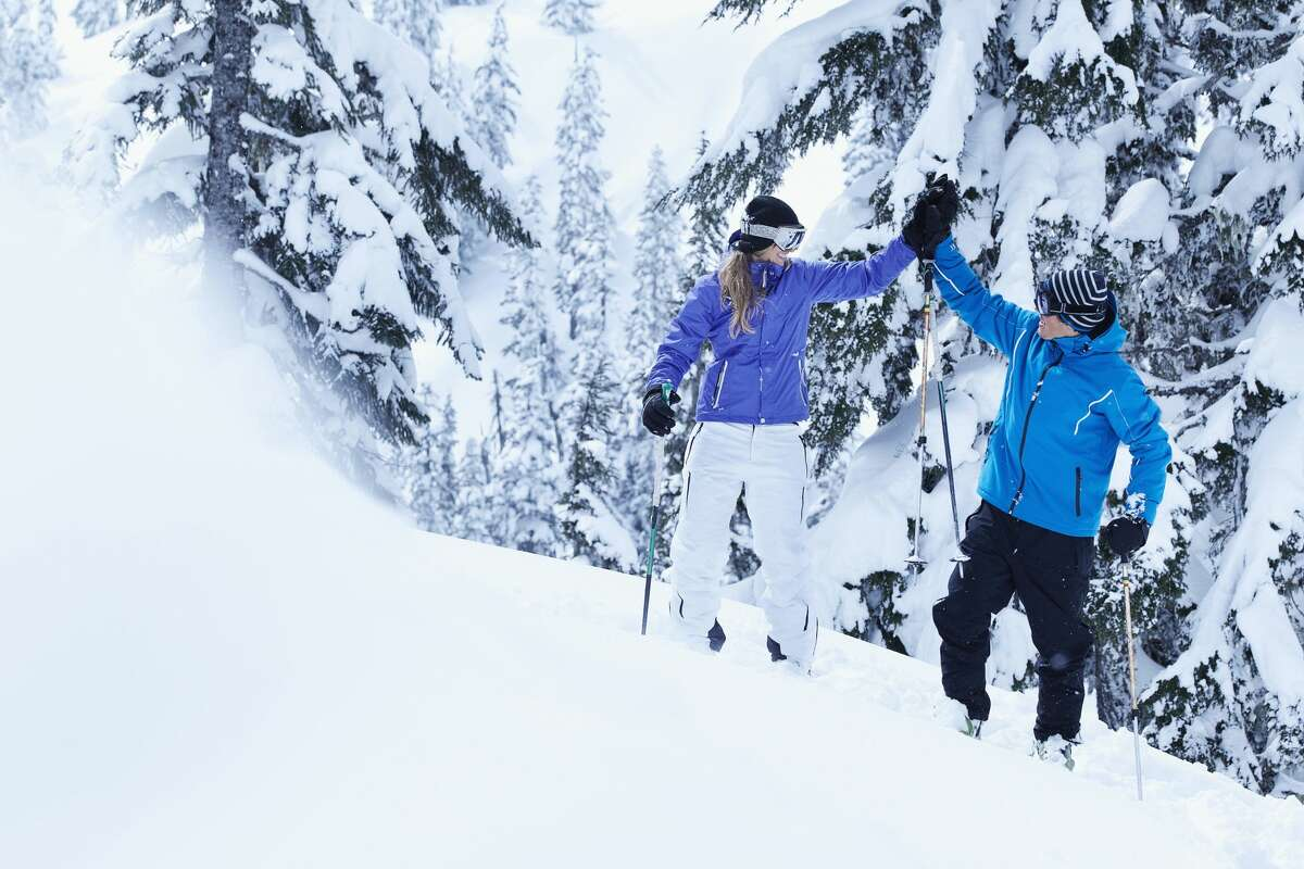 Skiers high-fiving on snowy mountain