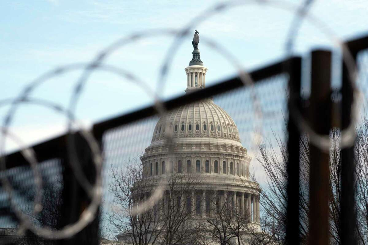 The U.S. Capitol seen through a fence and razor wire on Tuesday, the first day of arguments in the second impeachment trial of Donald Trump.