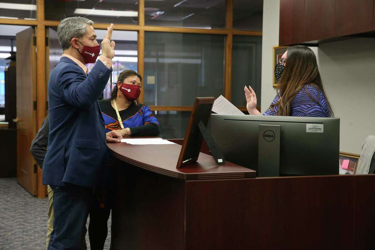 Mayor Ron Nirenberg, with wife Erika Prosper, takes the oath as he submits his application for re-election before city clerk official Lina Rodriguez.