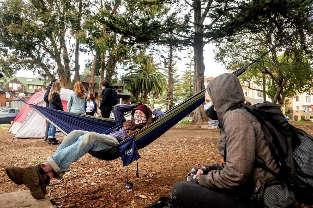 Coleman Rainey, a fourth-year Ph.D. student at Cal, lies in a hammock at People's Park. UC Berkeley's plans for the site are drawing protests.