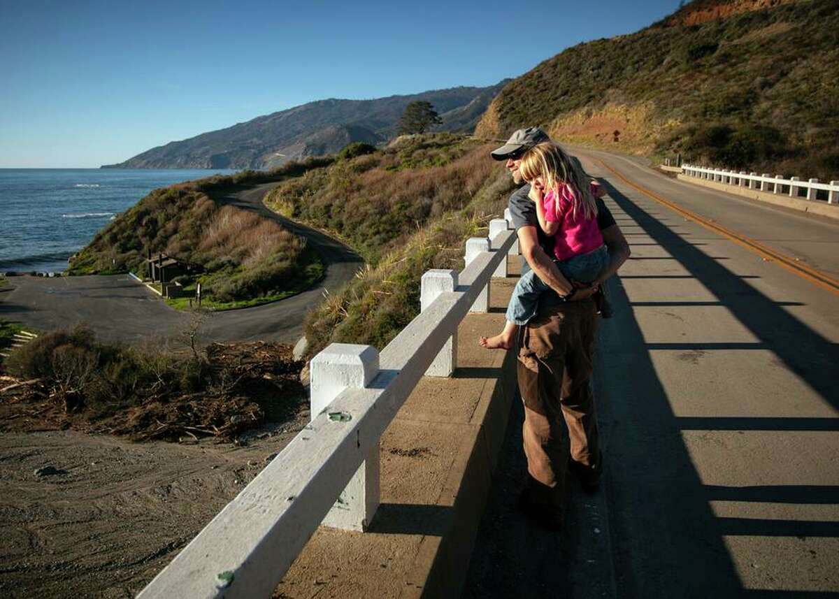 Local residents Mark Readdie and daughter Fiona walk along Highway 1 and look at a Mill Creek debris flow on Thursday.