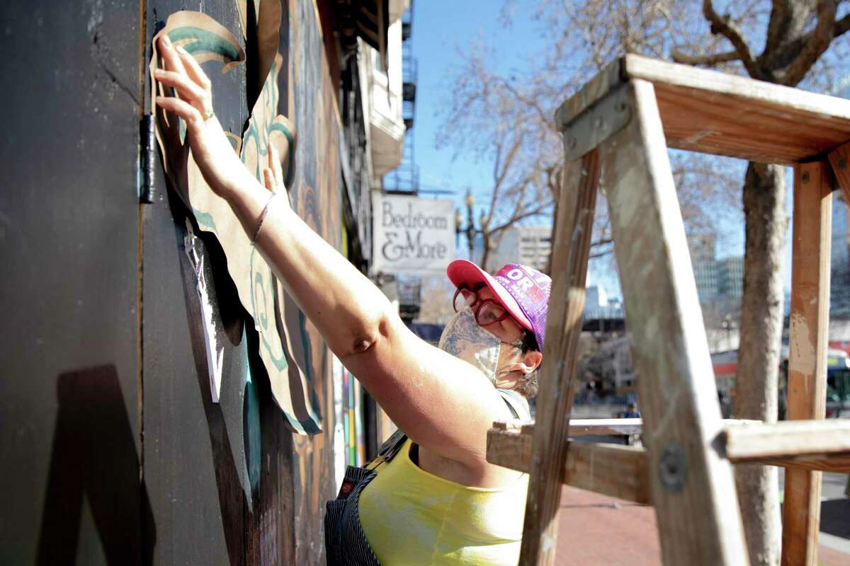 Artist Kaytea Petro affixes one of her murals outside of Green Arcade in San Francisco.