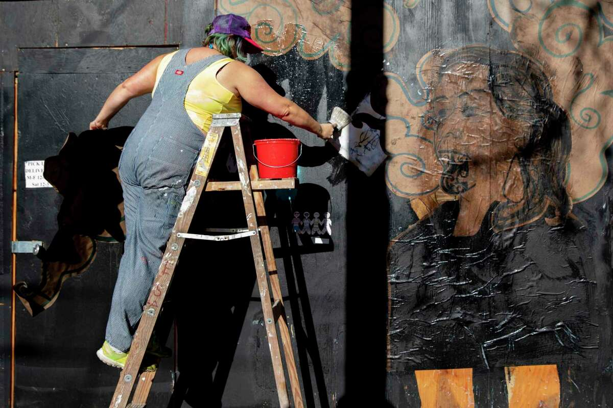 Artist Kaytea Petro works on a ladder to put finishing touches on one of her murals.
