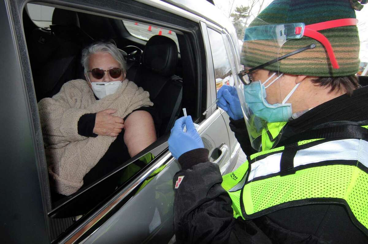 Toni Lamparski, of Shelton, receives the Pfizer vaccine hot from nurse Justin Leas, during Community Health Center's mass drive-through COVID-19 vaccination clinic held at the parking lot of Lord & Taylor in Stamford, Conn., on Wednesday Feb. 3, 2021.