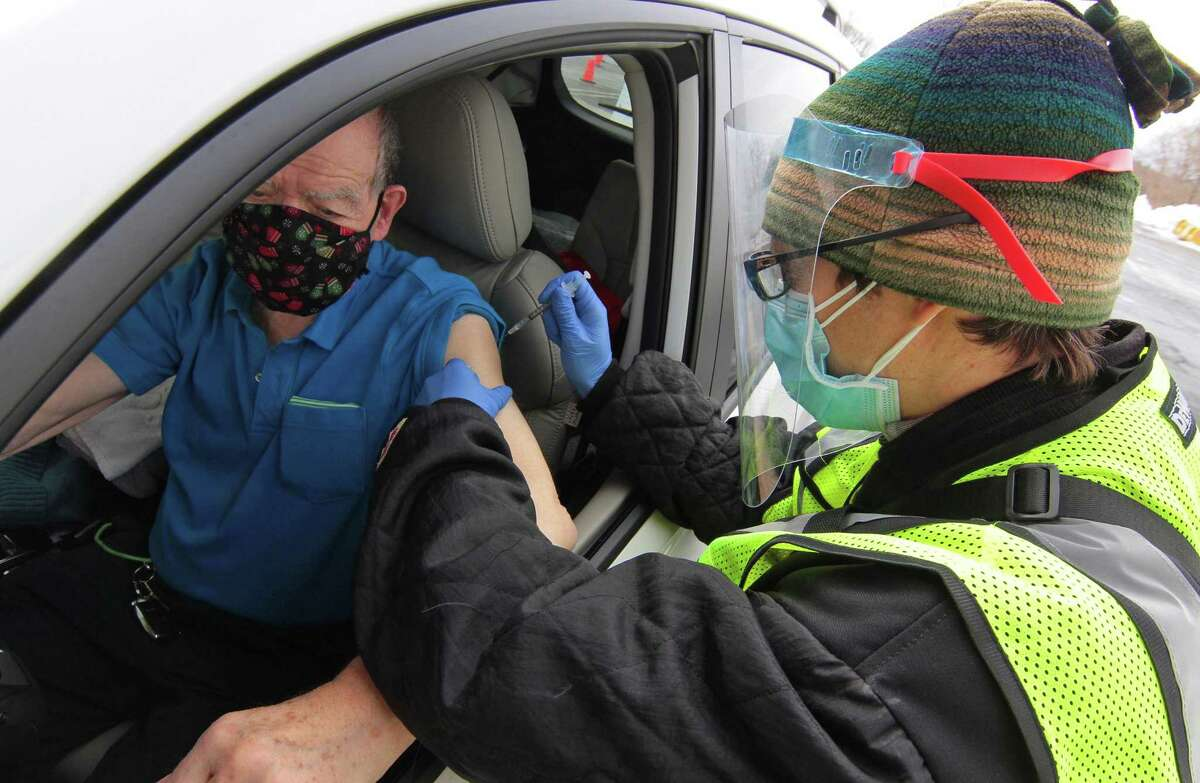 Thomas Juliusburger, of Stamford, receives the Pfizer vaccine shot from nurse Justin Leas, during Community Health Center's mass drive-through COVID-19 vaccination clinic held at the parking lot of Lord & Taylor in Stamford, Conn., on Wednesday Feb. 3, 2021.