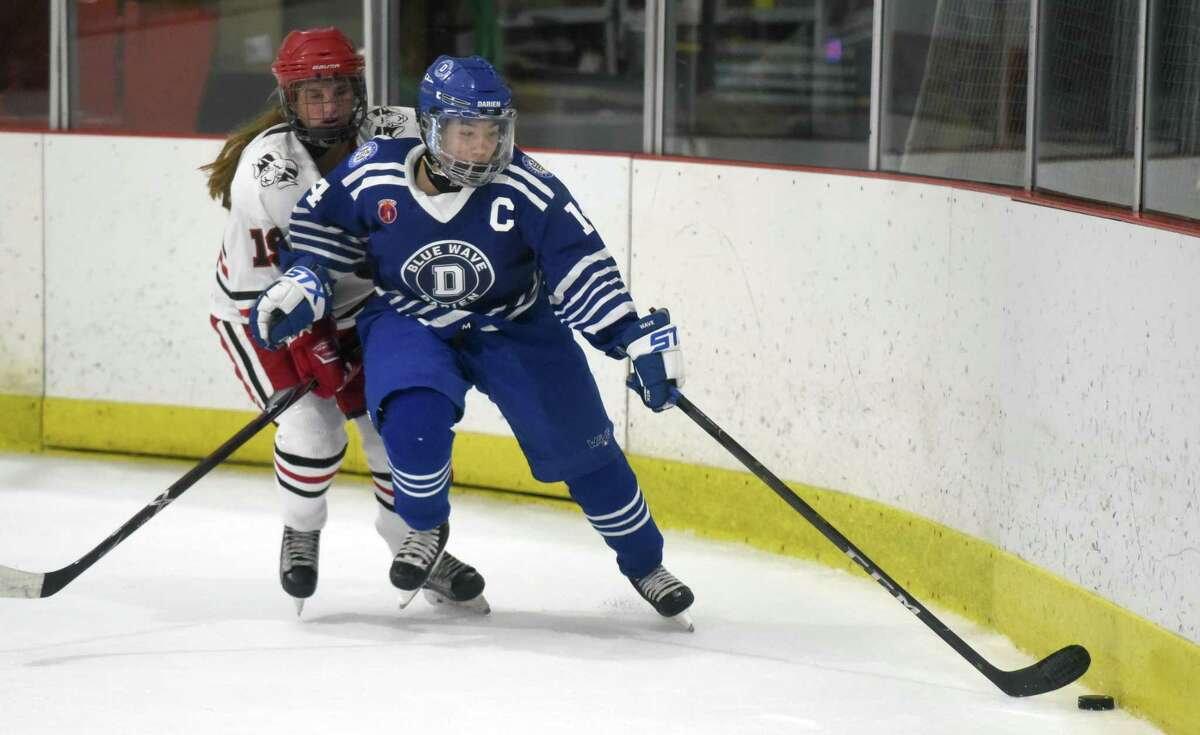 Darien's Cailtin Chan (14) gets to the puck in front of New Canaan's McKenna Harden (19) during a girls ice hockey game at the Darien Ice House on Saturday, Jan. 4, 2020.