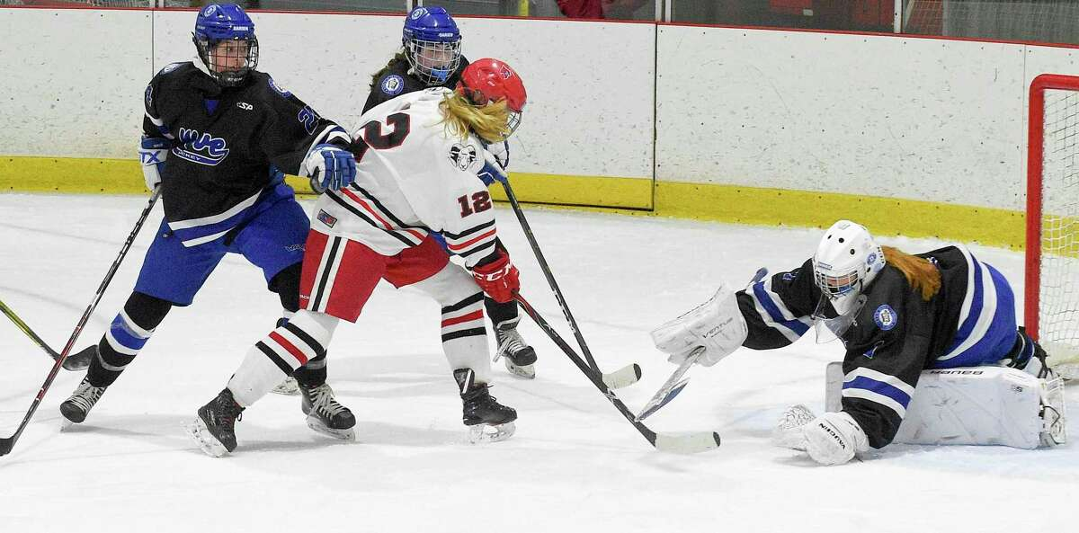 New Canaan's Amanda Benson (12) scores on Darien goalie Claire Haupt in the first period of the FCIAC Girls' Ice Hockey finals at the Darien Ice House in Darien, Conn., Saturday, Feb. 29, 2020. Darien defeated New Canaan 4-2.