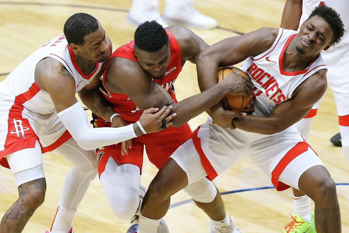 NEW ORLEANS, LOUISIANA - FEBRUARY 09: Zion Williamson #1 of the New Orleans Pelicans, Jae'Sean Tate #8 of the Houston Rockets and John Wall #1 go for a loose ball during the second half at the Smoothie King Center on February 09, 2021 in New Orleans, Louisiana.