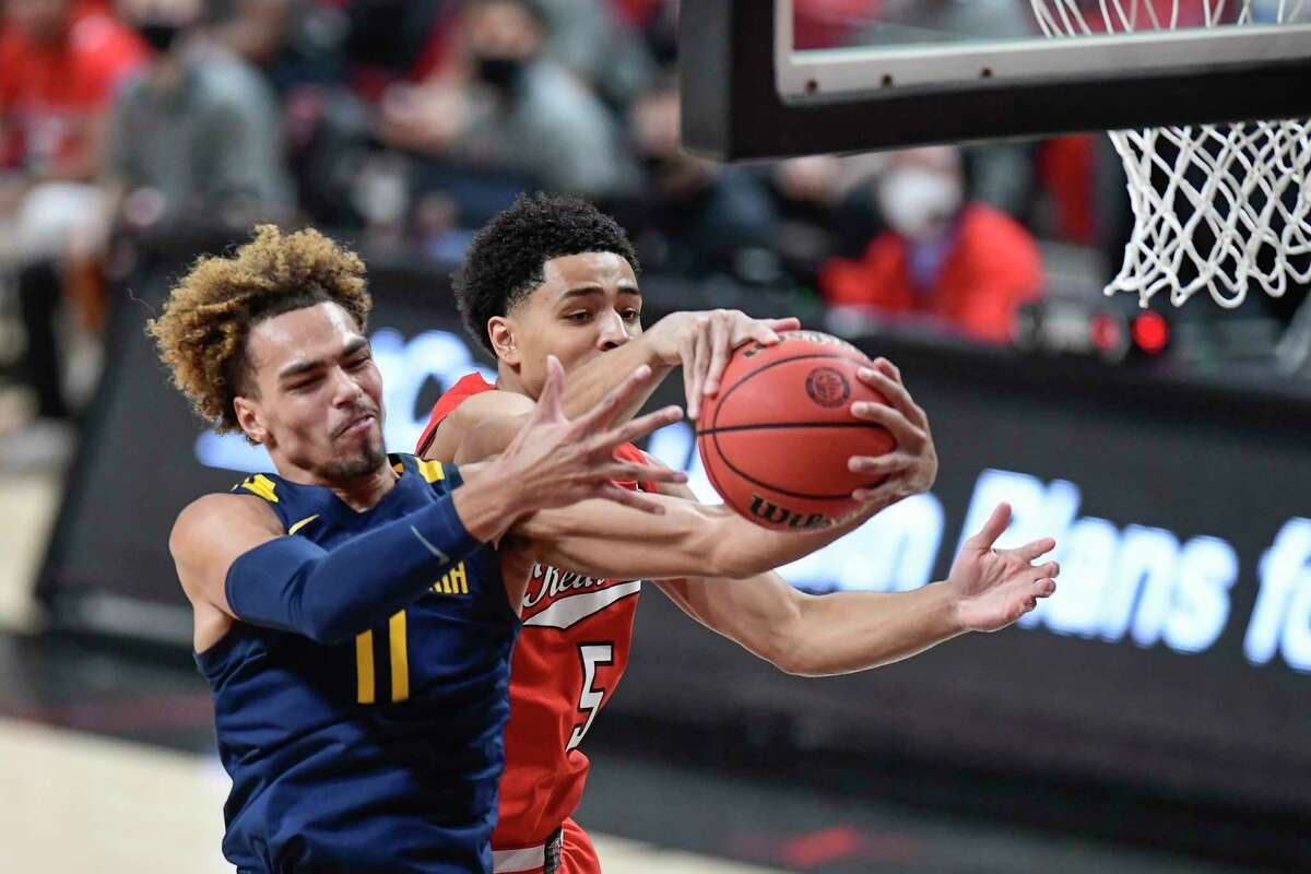 West Virginia's Emmitt Matthews Jr. (11) and Texas Tech's Micah Peavy (5) fight for a rebound during the first half of an NCAA college basketball game in Lubbock, Texas, Tuesday, Feb. 9, 2021. (AP Photo/Justin Rex)