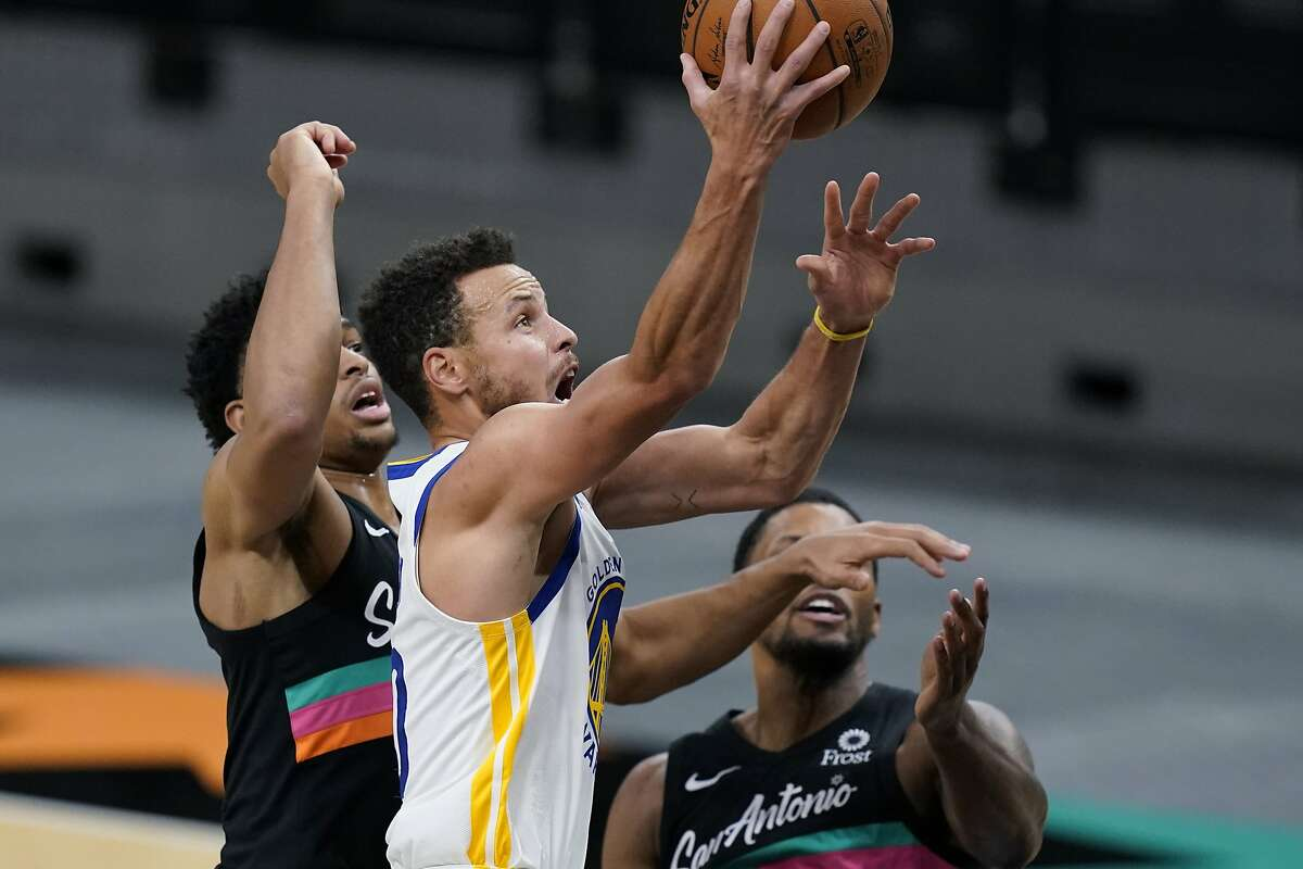 Stephen Curry glides past Keldon Johnson (left) and forward Rudy Gay during a commanding second-half performance at AT&T Center.