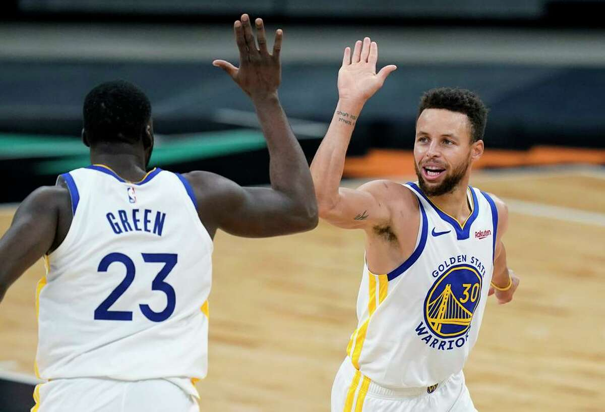 Golden State Warriors guard Stephen Curry (30) celebrates a score with teammate Draymond Green (23) during the second half of an NBA basketball game against the San Antonio Spurs in San Antonio, Tuesday, Feb. 9, 2021. (AP Photo/Eric Gay)