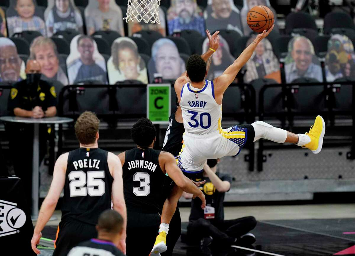 Golden State Warriors guard Stephen Curry (30) drives to the basket past San Antonio Spurs forward Keldon Johnson (3) during the first half of an NBA basketball game in San Antonio, Tuesday, Feb. 9, 2021. (AP Photo/Eric Gay)