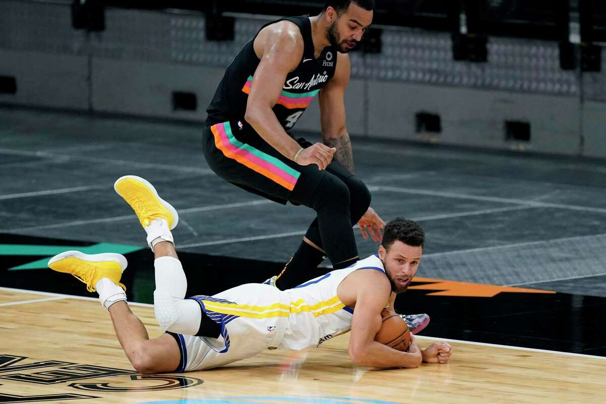 Golden State Warriors guard Stephen Curry (30) dives past San Antonio Spurs forward Trey Lyles (41) for a loose ball during the first half of an NBA basketball game in San Antonio, Tuesday, Feb. 9, 2021. (AP Photo/Eric Gay)