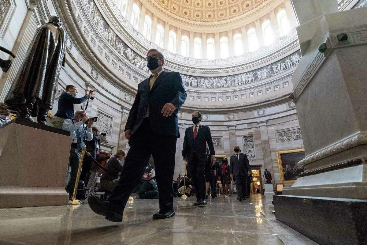 El sargento interino de armas Timothy Blodgett (izquierda) conduce al representante demócrata Jamie Raskin (segundo desde la izquierda), principal responsable demócrata de acusación en la Cámara de Representantes, y a otros responsables de acusación, a través de la Rotonda hacia el Senado para el segundo juicio político contra el expresidente Donald Trump, el martes 9 de febrero de 2021, en Washington.