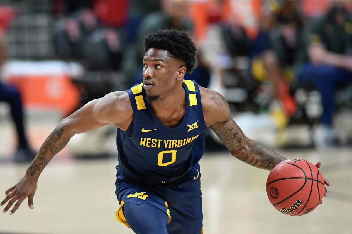 West Virginia's Kedrian Johnson (0) controls the ball during the first half of an NCAA college basketball game against Texas Tech in Lubbock, Texas, Tuesday, Feb. 9, 2021.