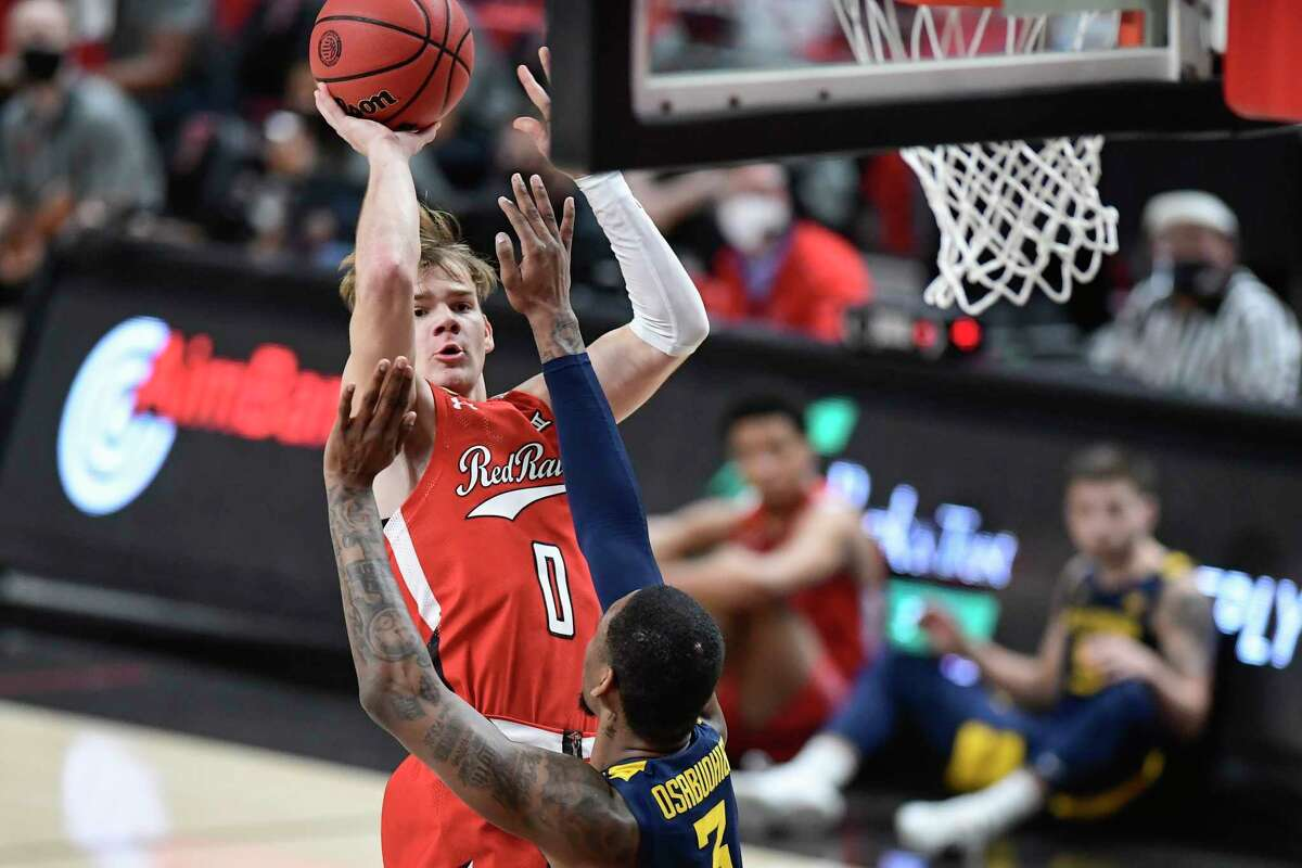 Texas Tech's Mac McClung (0) shoots the ball over West Virginia's Gabe Osabuohien (3) during the first half of an NCAA college basketball game in Lubbock, Texas, Tuesday, Feb. 9, 2021.