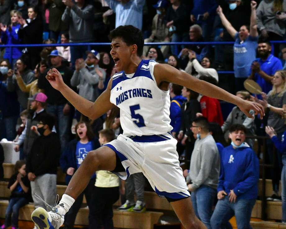 Olton's Israel Santillan celebrates the final seconds of the 13th-ranked Mustangs' 55-50 win over 15th-ranked Farwell to win the District 3-2A championship on Tuesday in Olton Memorial Gymnasium. Photo: Nathan Giese/Planview Herald