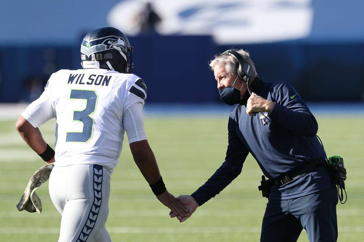 ORCHARD PARK, NEW YORK - NOVEMBER 08: Russell Wilson #3 high-fives head coach Pete Carroll of the Seattle Seahawks during the first half against the Buffalo Bills at Bills Stadium on November 08, 2020 in Orchard Park, New York. (Photo by Bryan M. Bennett/Getty Images)