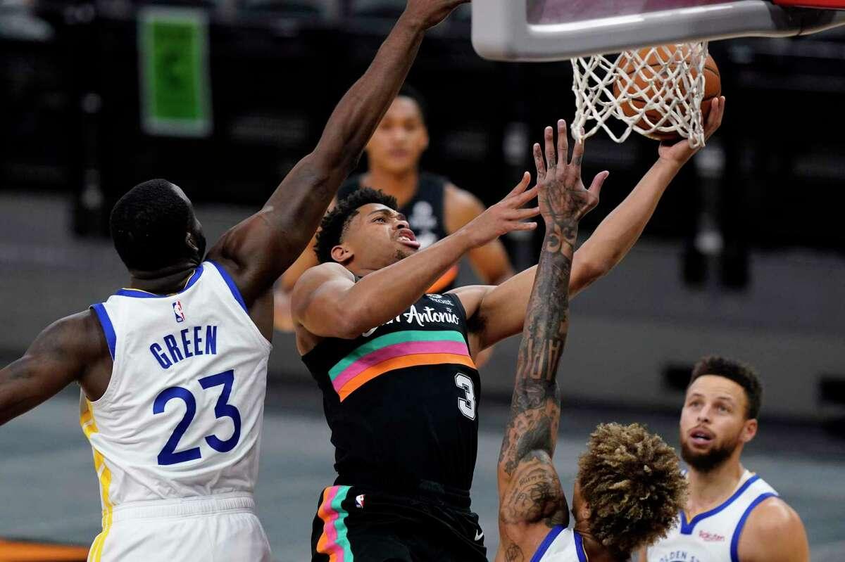 Spurs forward Keldon Johnson drives to the basket against Warriors forward Draymond Green.