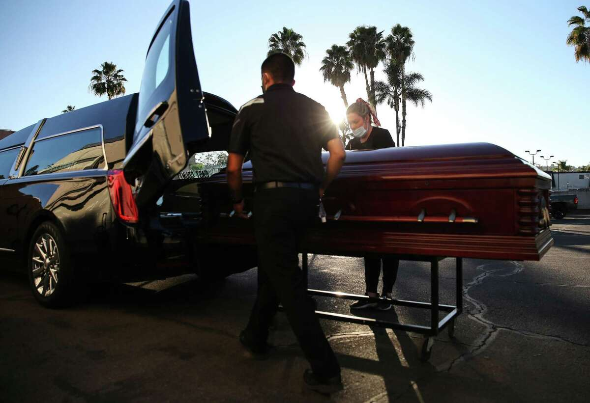 Funeral director Kristy Oliver (right) and funeral attendant Sam Deras load the casket of a person who died from COVID-19 into a hearse at East County Mortuary on Jan. 15 in El Cajon (San Diego County).