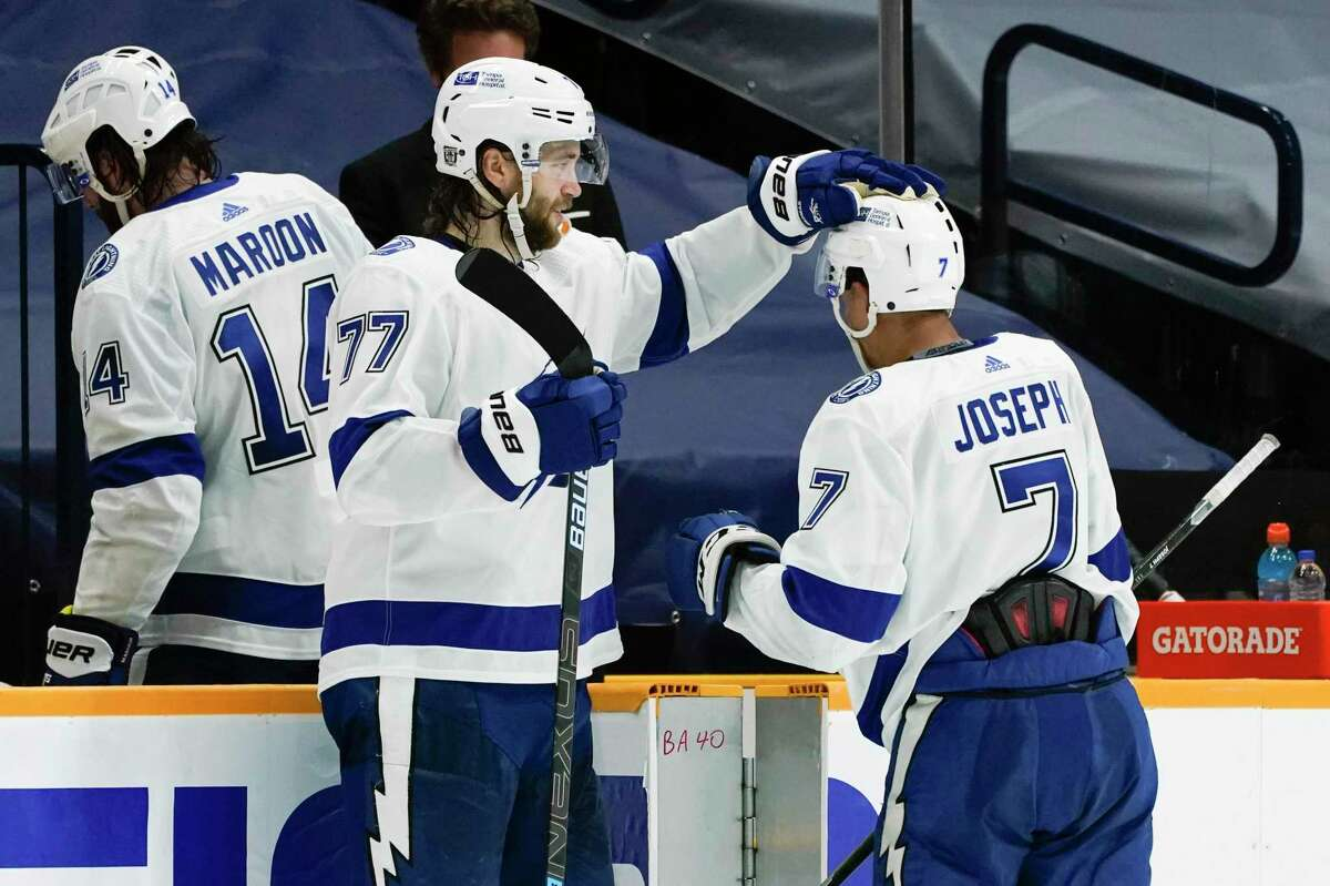 Tampa Bay Lightning right wing Mathieu Joseph (7) is congratulated by Victor Hedman (77) as the team leaves the ice after a 6-1 win over the Nashville Predators in an NHL hockey game Tuesday, Feb. 9, 2021, in Nashville, Tenn. Joseph had two goals in the win. (AP Photo/Mark Humphrey)