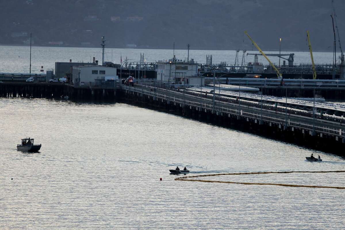 Chevron and fire-agency crews respond to a five-gallon-per-minute petroleum product leak in the waters of Point Richmond as an absorbent boom is placed next to the Chevron Richmond Long Wharf in Richmond, Calif., on Tuesday, Feb. 9, 2021.