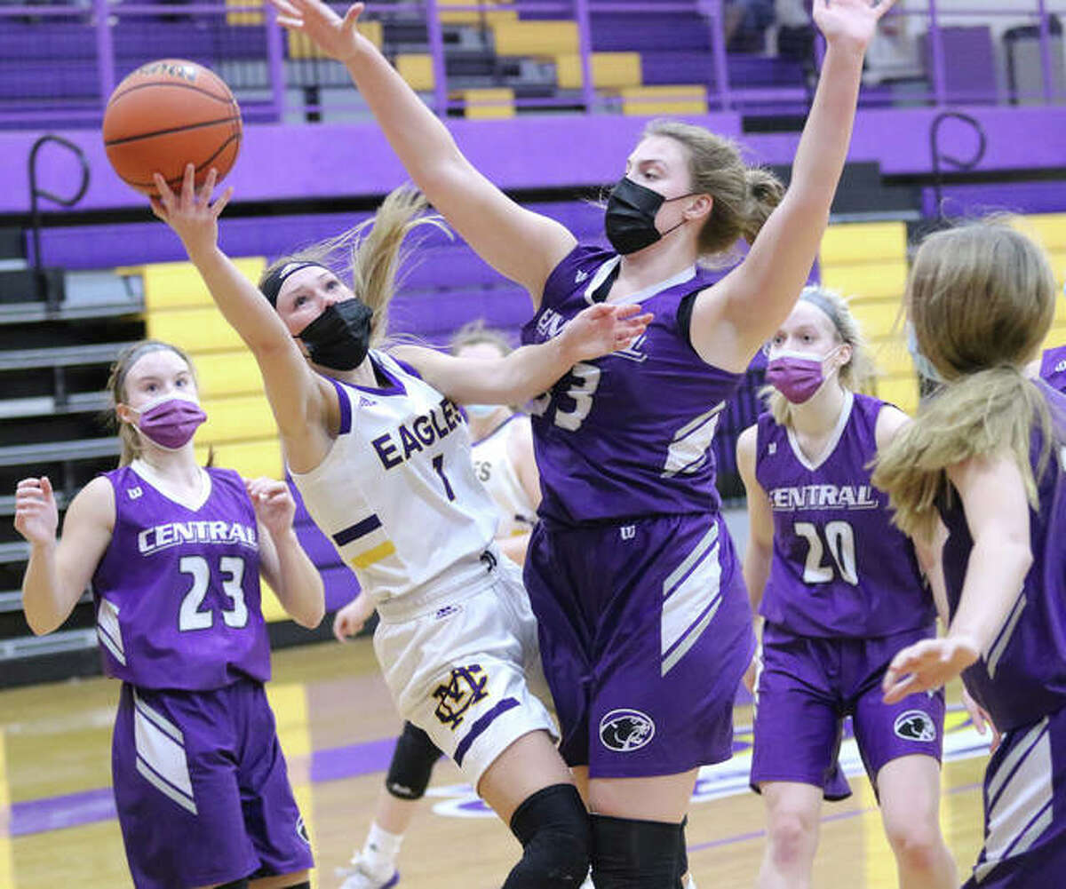 CM's Tori Standefer (1) scores as Breese Central's 6-3 Maggie Schrage contests the shot and Chloe Book (23) and Cassidy Kretschmer (20) watch the play in the first half Tuesday night in Bethalto