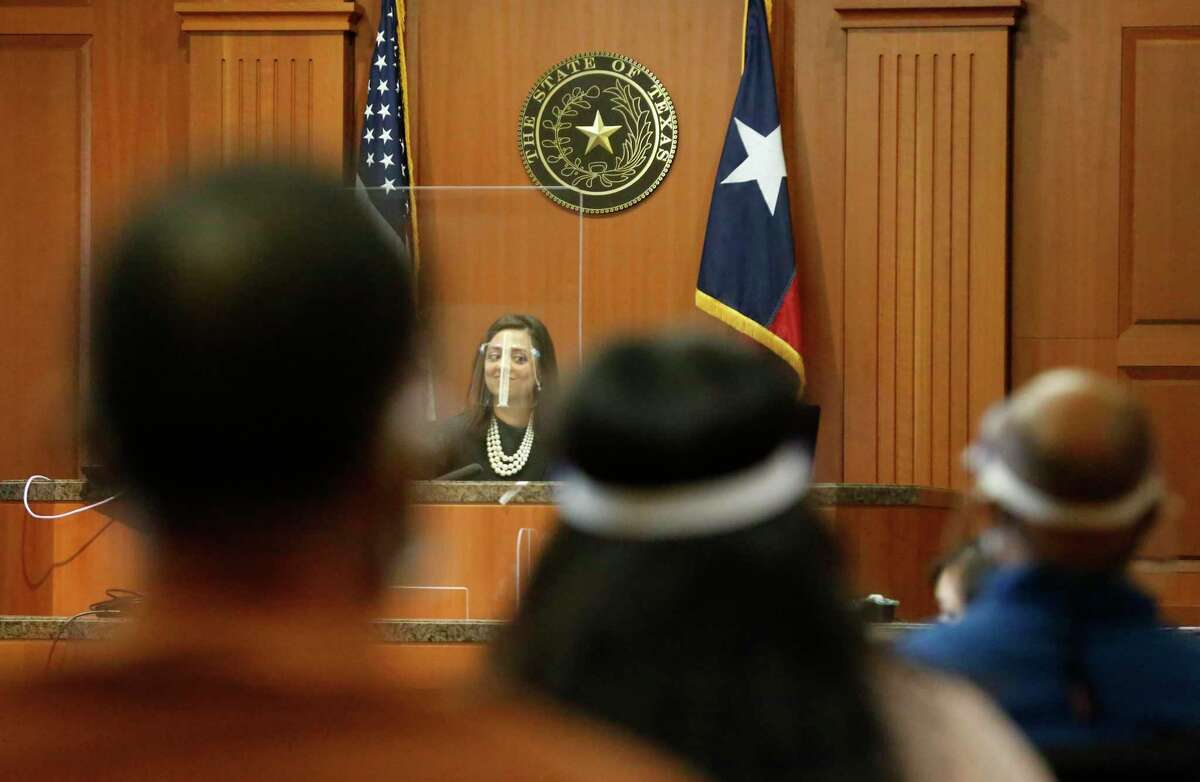 Harris County Judge Rabeea Sultan Collier wears a face shield and sits behind a plexiglass wall as the jurors sit in the gallery during a jury trial in the 113th court Wednesday, Feb. 3, 2021, in Houston.