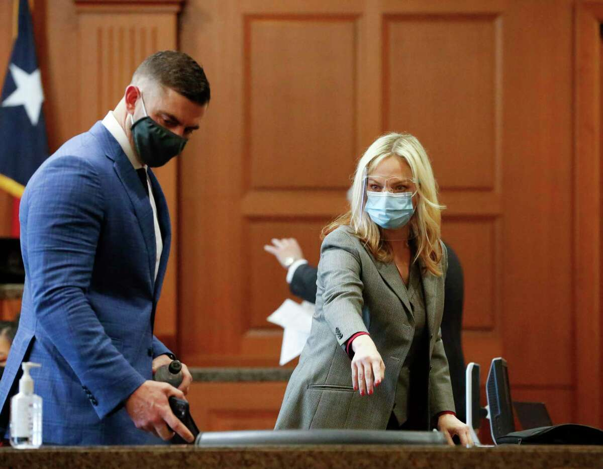 Attorney Claire Parsons wears a mask as she directs her defendant to a chair in Harris County Judge Rabeea Sultan Collier's courtroom Wednesday, Feb. 3, 2021, in Houston.