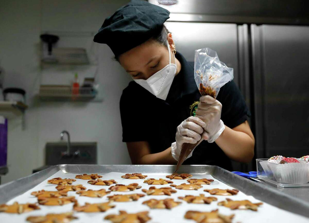 Isabella Macias pipes chocolate onto treats in preparations for Valentine's Day customers at Chocolate Passion, Tuesday, Feb. 9, 2021, in Conroe.