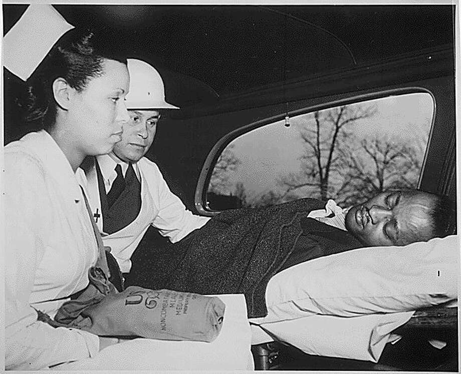 """After receiving first aid treatment in a practice raid in Washington, D.C., an air-raid """"victim"""" was taken to the hospital by a Medical Corps of the Office of Civilian Defense. The physician is Dr. Charles Drew (middle).(Courtesy photo/National Archives)"""
