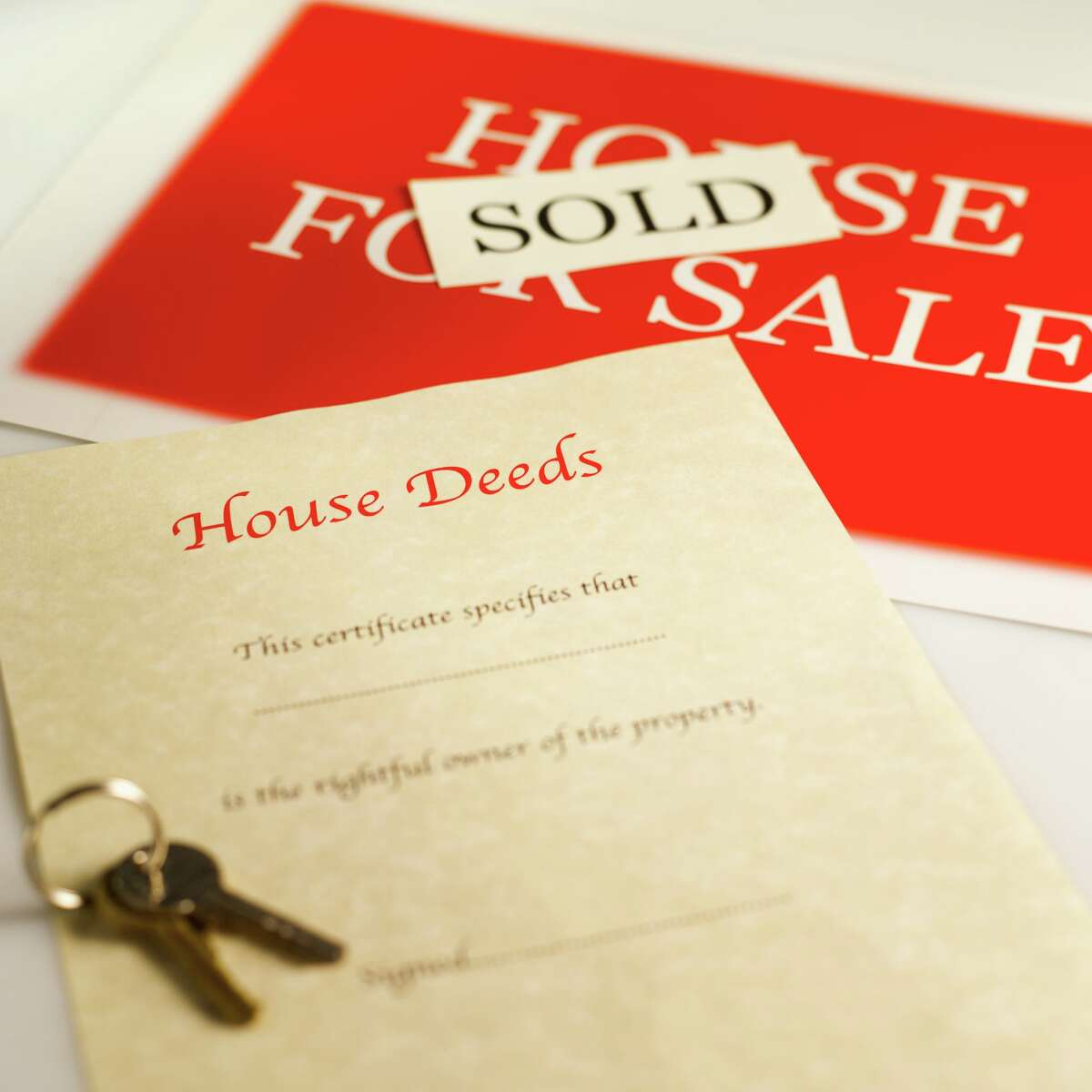 Close-up of house deeds and keys with house for sale sign and sold sticker attached