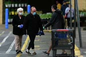 Shoppers come in and out of Walmart Saturday, March 28, 2020, in Norwalk, Conn.