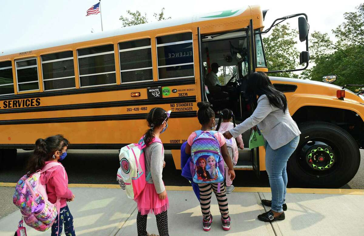 School staff help students boarding buses at Fox Run Elementary School Thursday, September 16, 2020. Norwalk Public Schools is working out the kinks in their bussing after adding bus monitors to help enforce COVID guidelines. To do this, the district is keeping on their seasonal help in the Transportation Department until October.